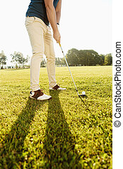 Cropped image of a golfer putting golf ball on green