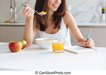 Cropped image of a smiling woman eating cereal