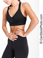 Cropped image of a sportswoman suffering from stomach pain