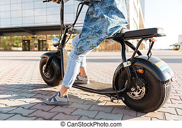 Cropped image of a woman sitting on a motor bicycle
