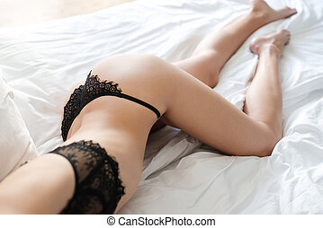 Cropped image of amazing sexy woman lies on bed