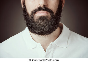 Cropped image of bearded man over dark background