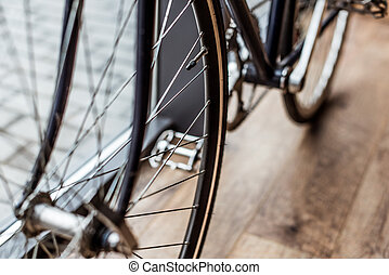 cropped image of bicycle on wooden floor in house