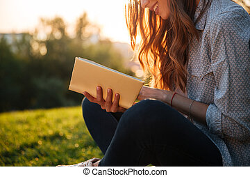 Cropped image of brunette woman sitting on bench