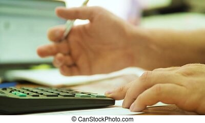 Cropped image of businessman using calculator in office....