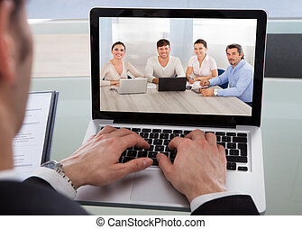 Cropped image of businessman using laptop at desk in office