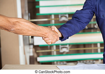 Cropped Image Of Carpenters Shaking Hands - Cropped image of...