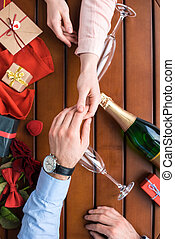 cropped image of couple holding hands at table with presents