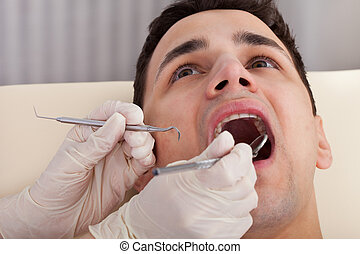 Cropped Image Of Dentist Examining Patient's Mouth