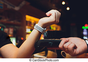 Cropped image of female customer paying through smart watch at bar.