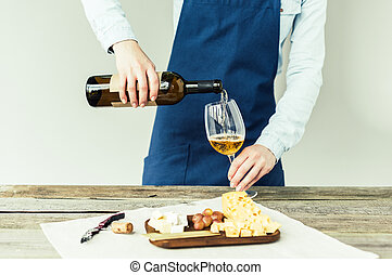 sommelier pouring white wine into glass