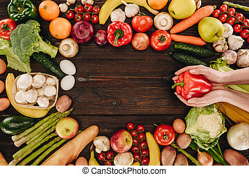 cropped image of girl holding bell pepper above vegetables and fruits on wooden table