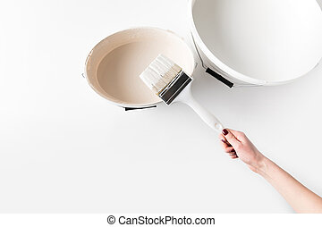 cropped image of girl holding brush in white paint on bucket isolated on white