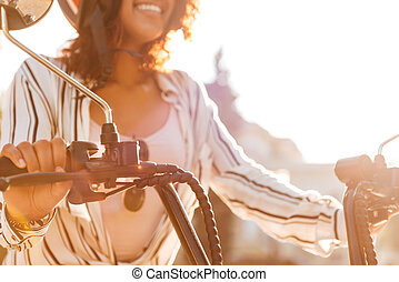 Cropped image of happy african woman sitting on modern motorbike