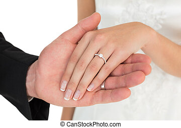 Cropped image of newly wed couple holding hands over while ...