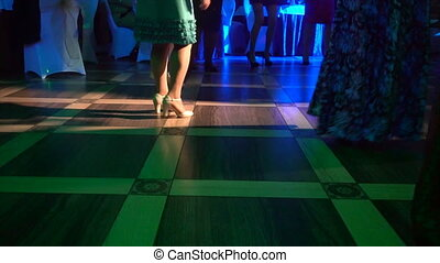 Cropped image of people's feet dancing on a floor .