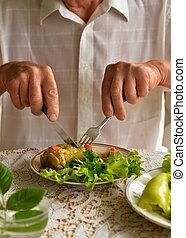 Cropped image of senior man eating