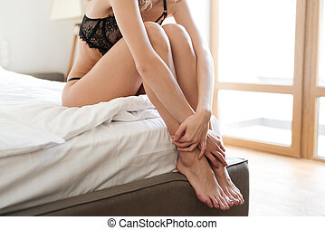 Cropped image of sexy woman sitting on bed