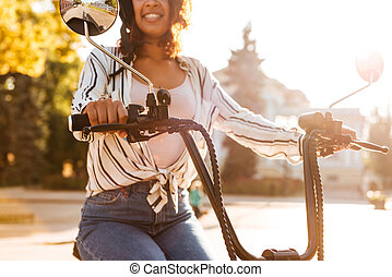 Cropped image of smiling african woman sitting on modern motorbike