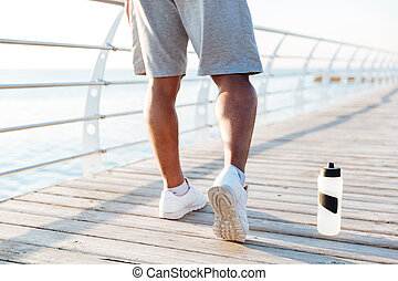 Cropped image of sports men legs doing exercises outdoors