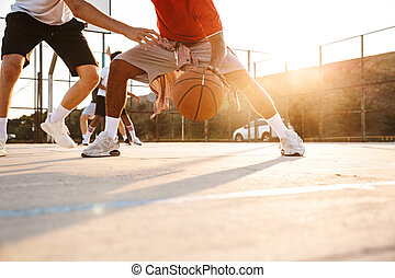 Cropped image of strong multiethnic men basketball players ...