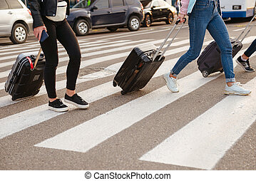 Cropped image of three women walking across pedestrian crossing, and carrying luggage after arrival to airport. Air travel or holiday concept
