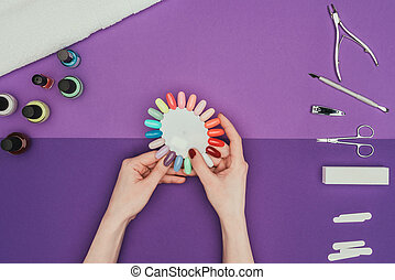 cropped image of woman choosing color for nails with manicure palette