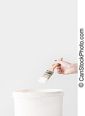 cropped image of woman holding brush in white paint above bucket isolated on white