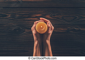 cropped image of woman holding candle above wooden table