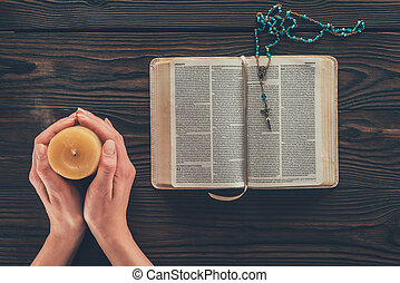 cropped image of woman holding candle above wooden table with bible