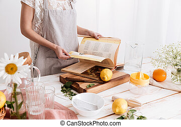 Cropped image of woman holding cooking book