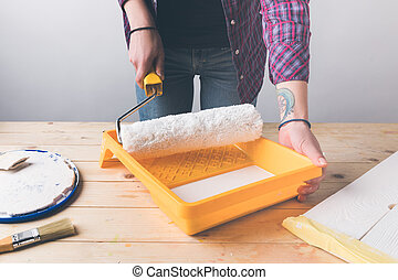 cropped image of woman holding paint roll brush above tray with paint