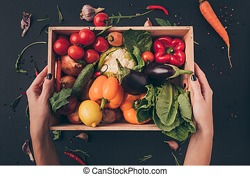 cropped image of woman holding wooden box with vegetables