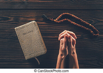 cropped image of woman sitting at table with rosary and holy bible and praying