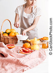 Cropped image of woman squeezes out juice of a citruses.