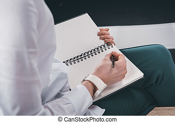 woman writing notes in notepad