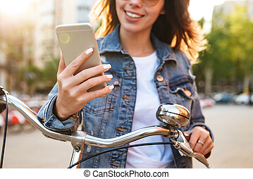 Cropped image of young beautiful lady using mobile phone.