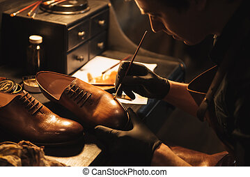 Cropped image of young concentrated man shoemaker at ...