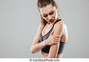 Cropped image of young fitness woman having arm pain