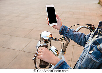 Cropped image of young lady outdoors using mobile phone.