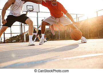 Cropped image of young multiethnic men basketball players ...