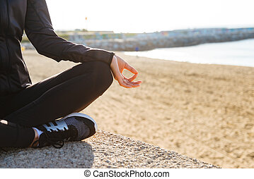 Cropped image of young sports woman sitting outdoors