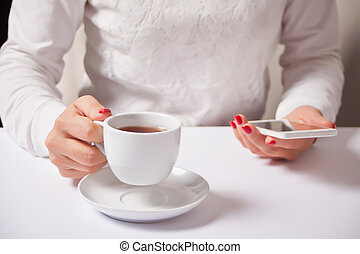 Cropped image of young woman sitting at a table with a coffee or tea and using mobile phone