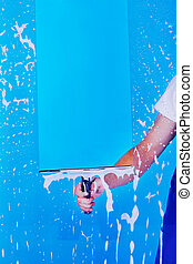 Cropped image male servant cleaning glass with squeegee over blue background