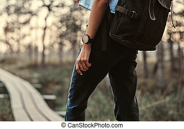 Cropped photo of a tourist girl with backpack walk on a wooden footpath in beautiful forest.