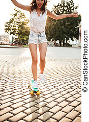Cropped photo of amazing young woman with skateboard