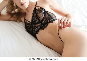 Cropped photo of sexy woman lies on bed