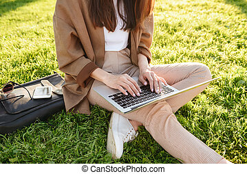 Cropped photo of woman sitting on grass using laptop computer.