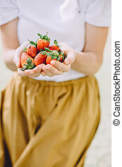 Cropped photo of young woman eating fresh strawberries at picnic
