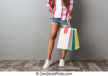 Cropped photo of young woman holding shopping bags